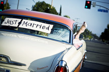 """Bride and groom in classic car with """"Just Married"""" in back window brides foot hanging out window"""