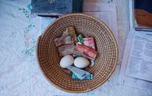 offering basket - This women put two eggs in the basket.