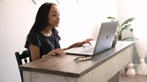 a young woman working from home on a video conference