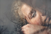 double exposure of a bare tree and woman's face - sorrow