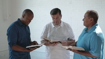 a group of men reading Bibles and discussing scripture