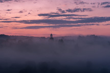 morning mist over a lake at sunrise and distant steeple