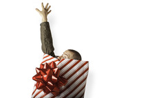 Christmas consumerism - man wrapped in Christmas paper reaching out for help