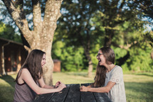 teen girls talking and laughing sitting at a picnic table