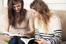 Friends reading a Bible together on a couch.