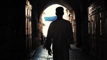 man walking the narrow streets of Via Dolorosa, Israel