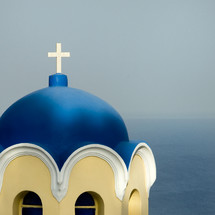 A vivid blue steeple with the ocean horizon line in the distance