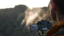 man filming a mountain with a video camera