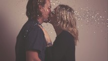 a couple kissing under falling confetti