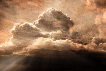 rays of sunlight through clouds over a mountain peak