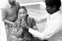 young woman being dunked in water during a baptism