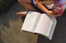 a boy child reading a Bible