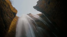 looking up at a rushing waterfall over a cliff