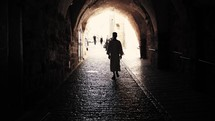 man walking the streets on Via Dolorosa, Israel