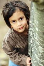 Boy standing behind tree trunk