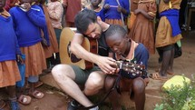man teaching a child how to play a guitar