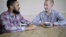 two men having a conversation over coffee