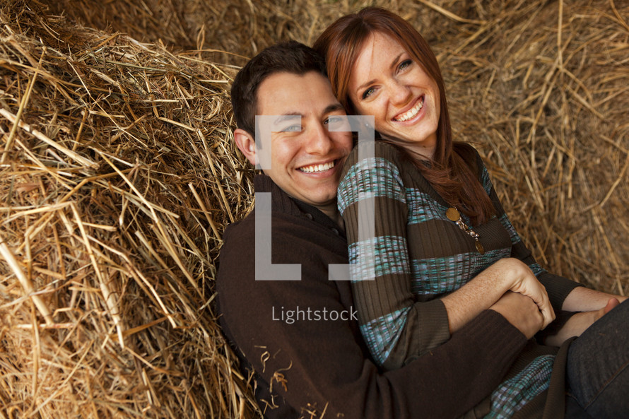 a couple snuggling in hay