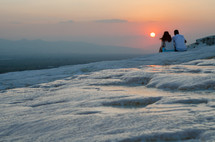couple sitting on top of Pamukkale (cotton castle) in Turkey, looking out at a sunset