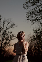 woman standing in the woods at sunset