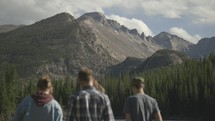 youth at the edge of a lake enjoying mountain views