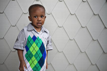 Boy posing in front of wall