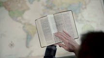 a man reading a Bible over a map