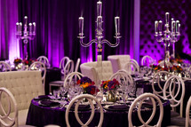 place setting at a set table formal dining, purple decor drapes, crystal centerpiece