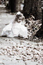 Young girl touching leaves in the park