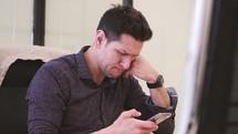 man sitting at his desk texting