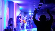 musicians on stage and hands raised during a worship service