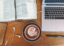 an open Bible, a laptop computer with earbuds, a pen, and a cappuccino