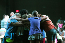 embracing in a prayer circle