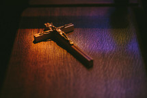 Crucifix sitting in colored light on a pew in a Roman Catholic church