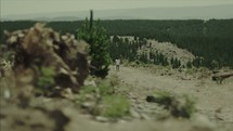 teen girl walking through a clearcut bare forest dragging a stick