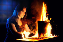 woman looking at a computer screen that is on fire