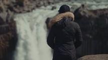 a woman watching a waterfall