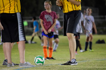 a girl playing soccer standing next to referees
