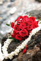 Bouquet of red roses and a lei on a rock