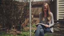 woman sitting on a park bench reading a Bible
