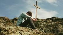 a man praying on a mountainside beside of a cross