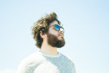 side profile of a man with a beard in sunglasses