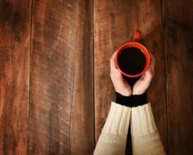 women holding a coffee mug over a wood table