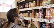 a woman grocery shopping wearing a face mask