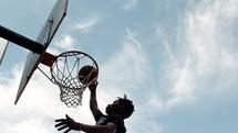 an African American man dunking a basketball
