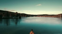 man standing on a lake shore looking out