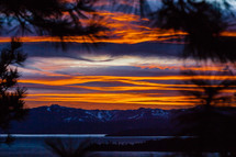 View thru pine trees of snow capped mountains lake & clouds at  orange sunset lake