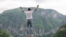 a man raising hands standing outdoors worshiping God