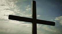cross against a blue sky at sunrise