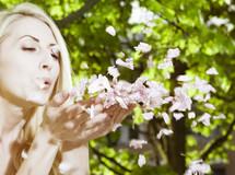 woman blowing petals; floating petals